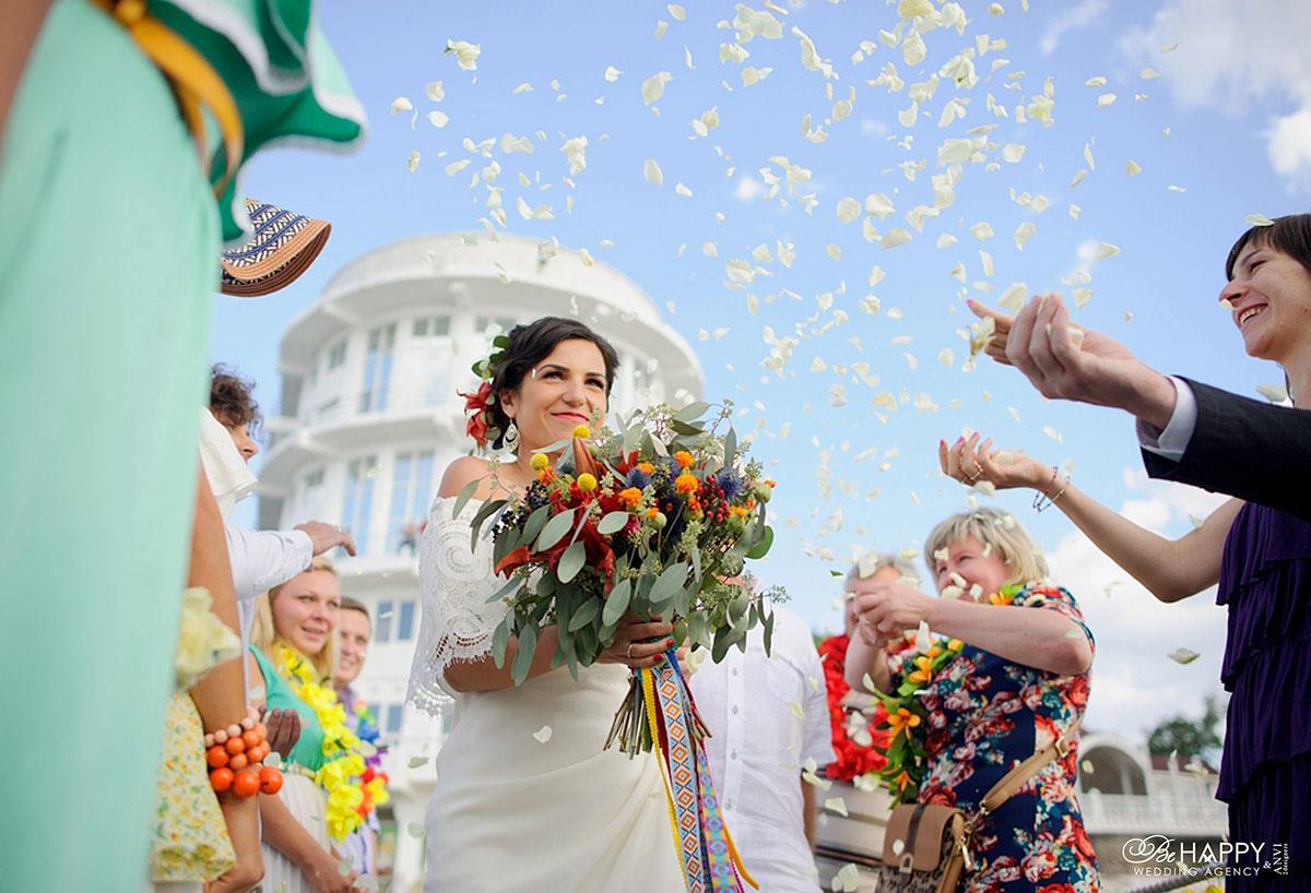 Невесту посыпают лепестками роз на выездной свадебной церемонии