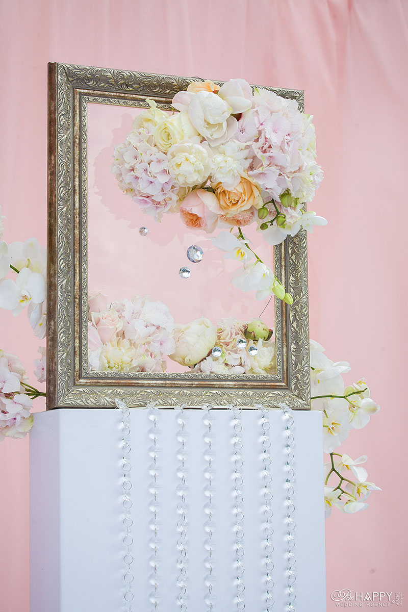 Зона проведения свадебной церемонии с декоративной рамкой, живыми цветами и бусами