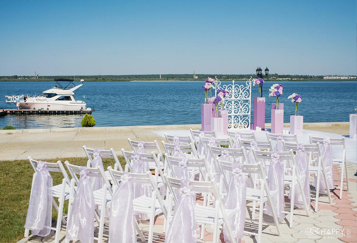Места для рассадки гостей свадебной церемонии на фоне реки