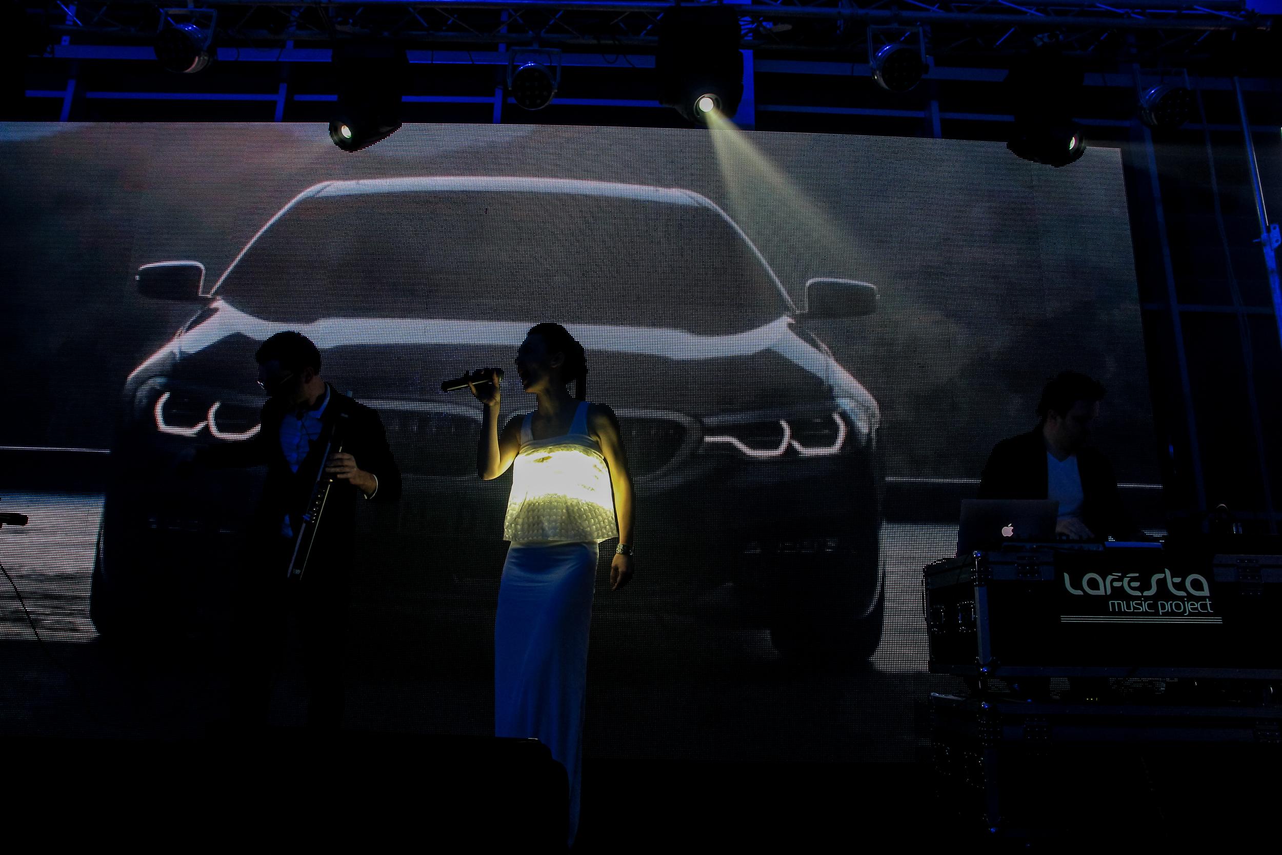 Выступление музыкального коллектива на фоне изображение BMW 5-Серии