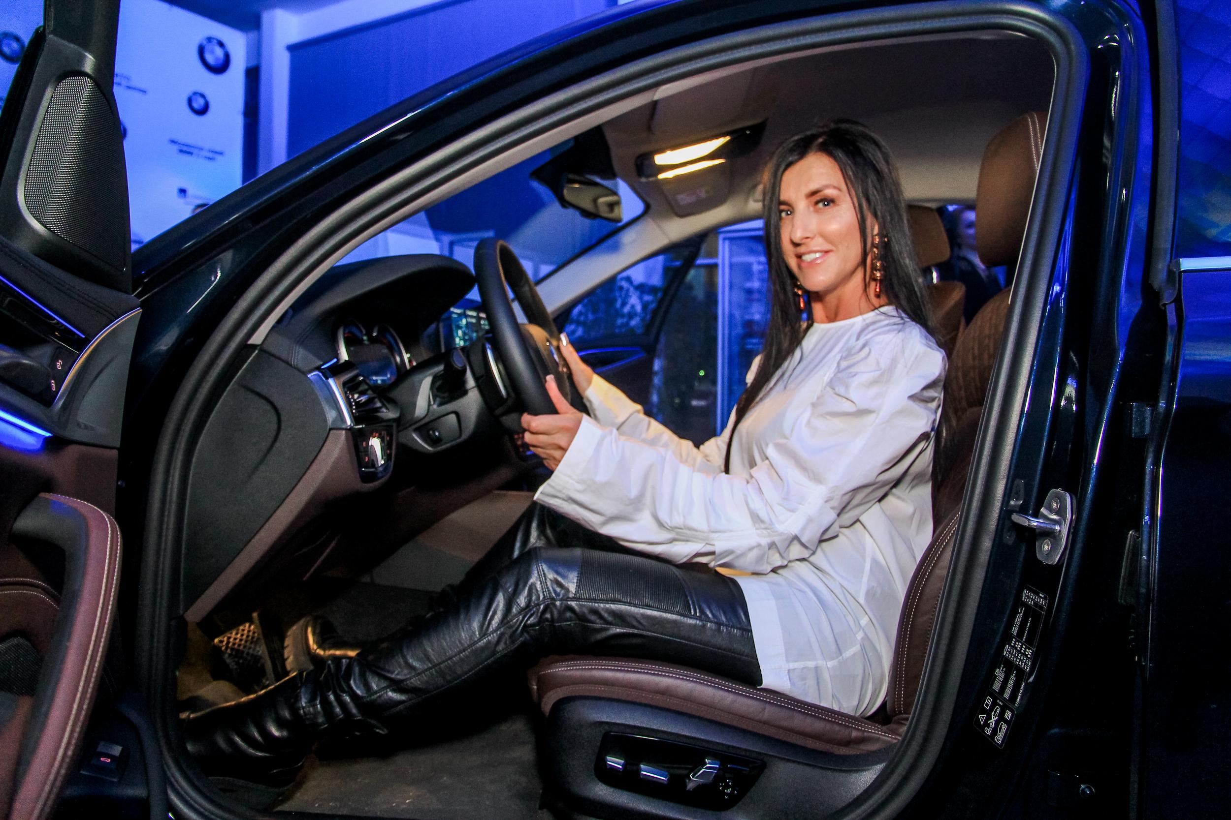 Очаровательная гостья презентации BMW за рулем автомобиля