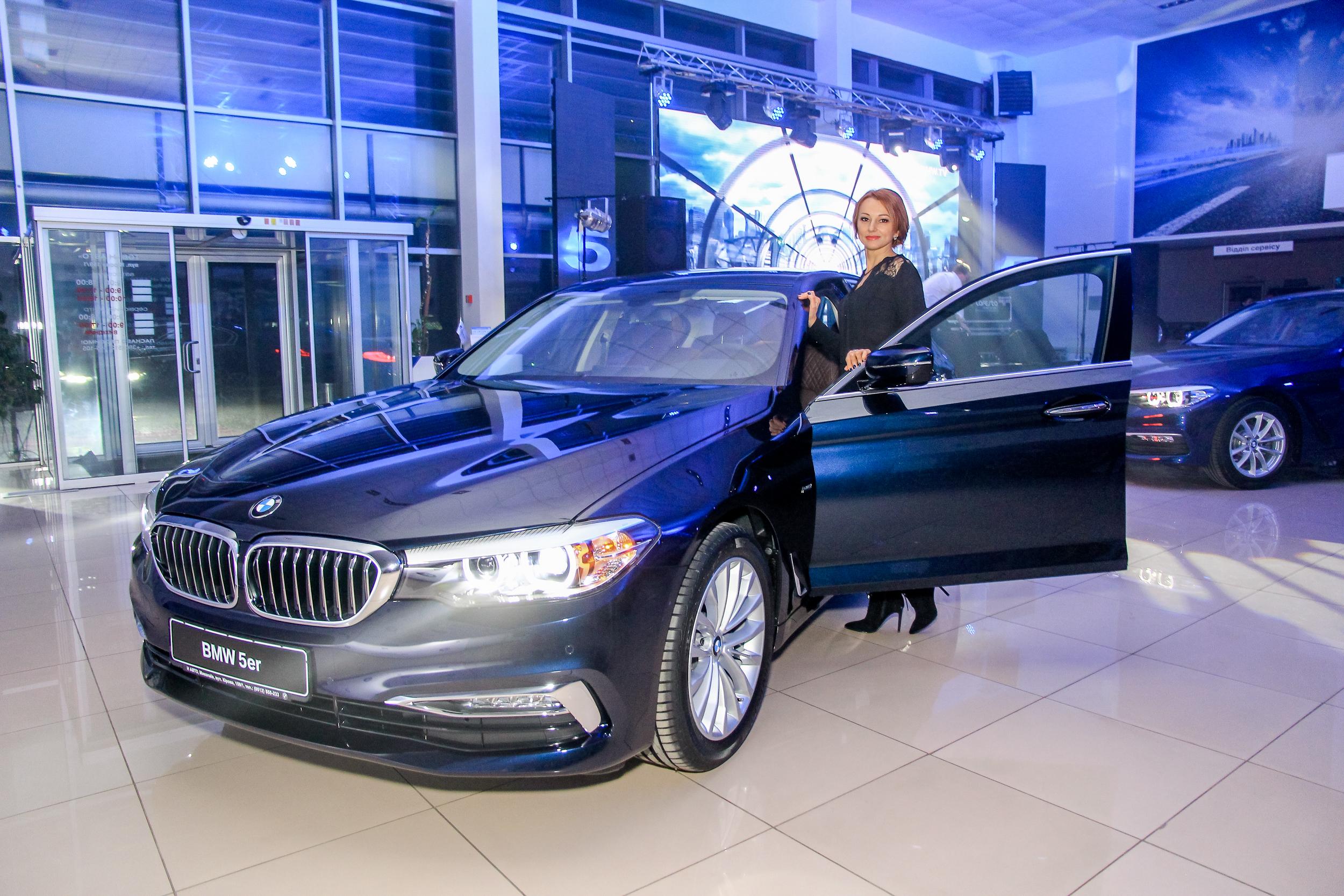 Гостья презентации BMW 5-Серии возле нового автомобиля