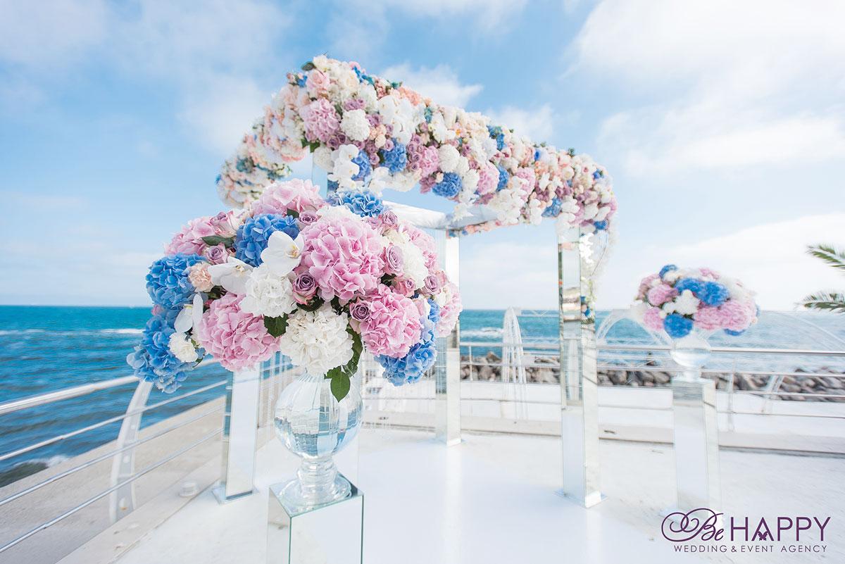 Свадебная арка, украшенная живыми цветами на фоне реки
