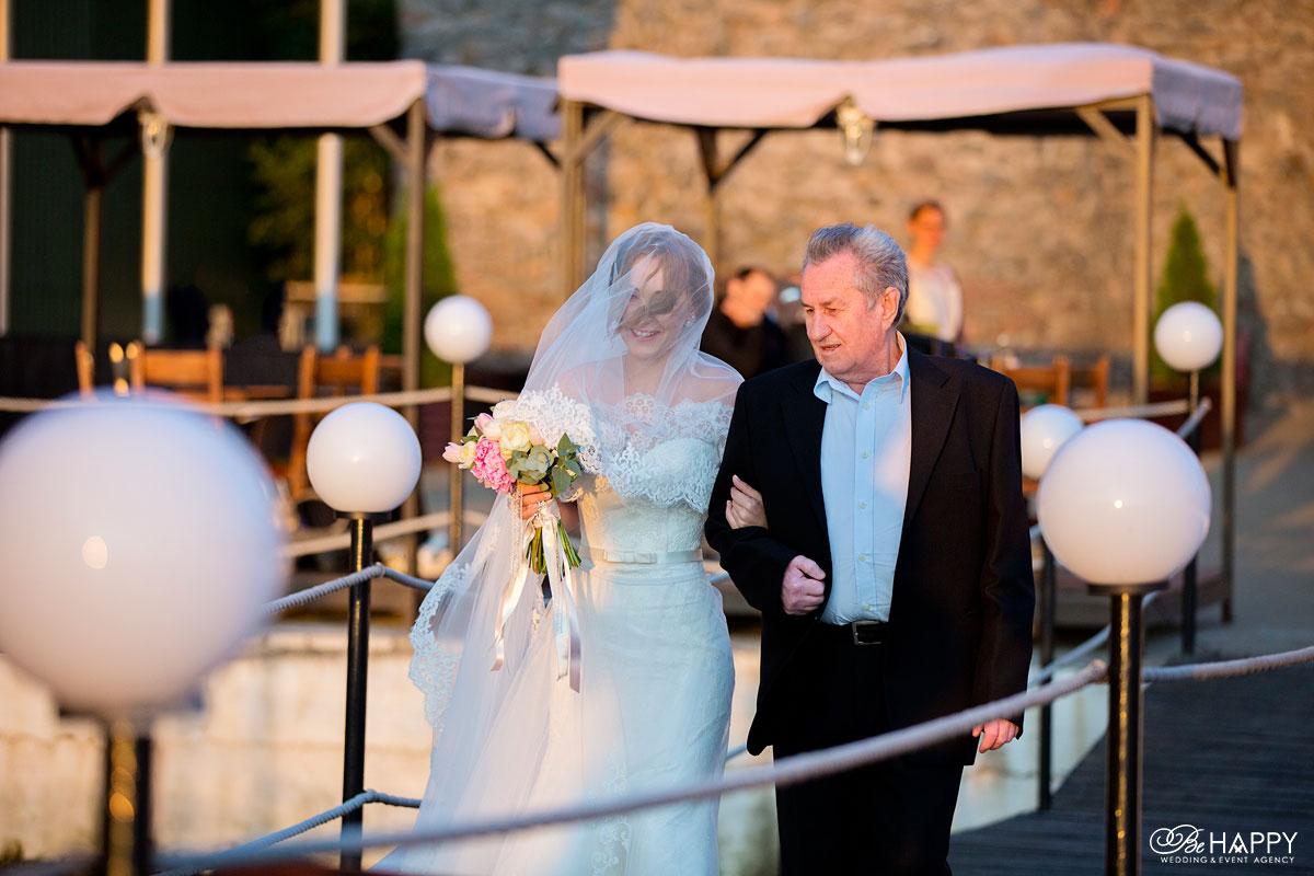 Отец невесты ведет ее к месту проведения церемонии