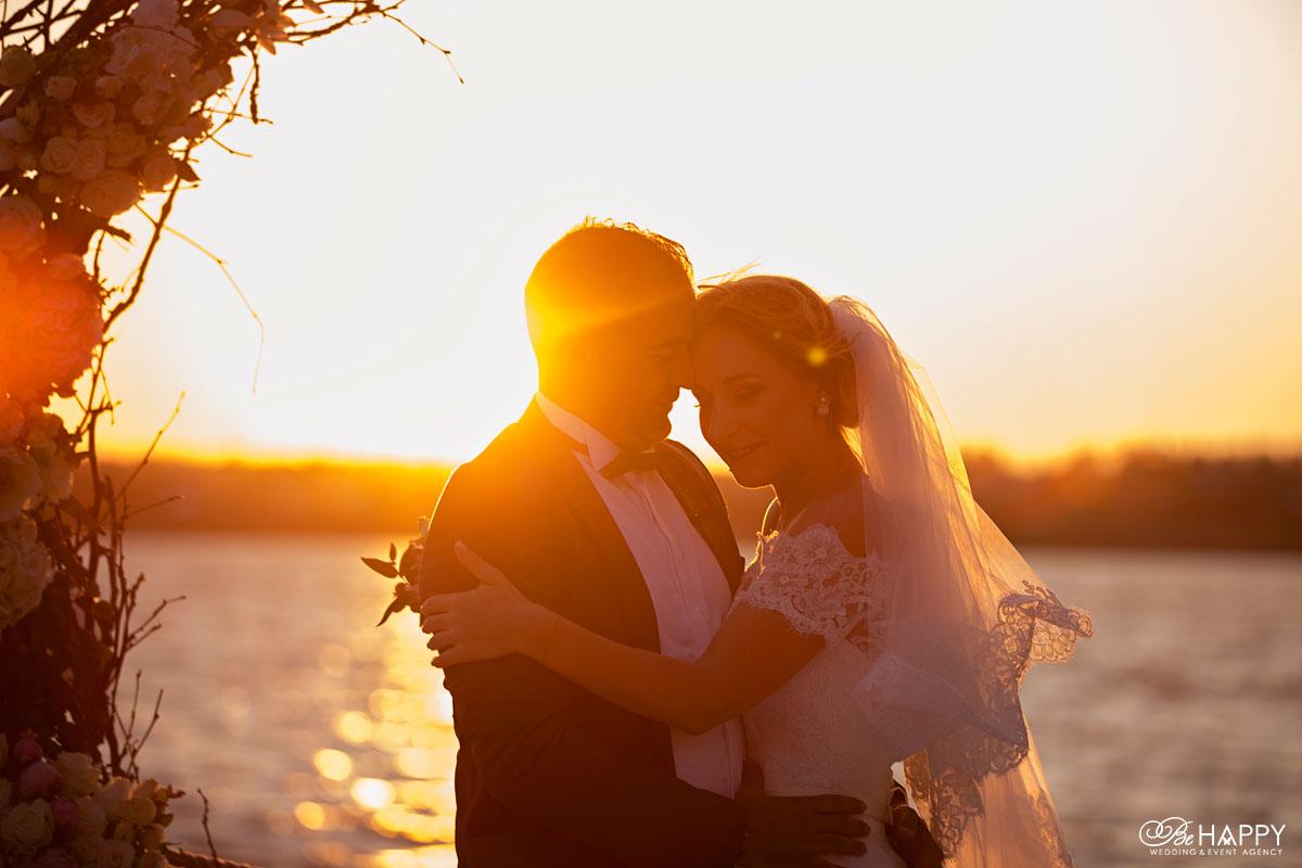Обнимающиеся жених и невеста в лучах заката свадьба Николаев
