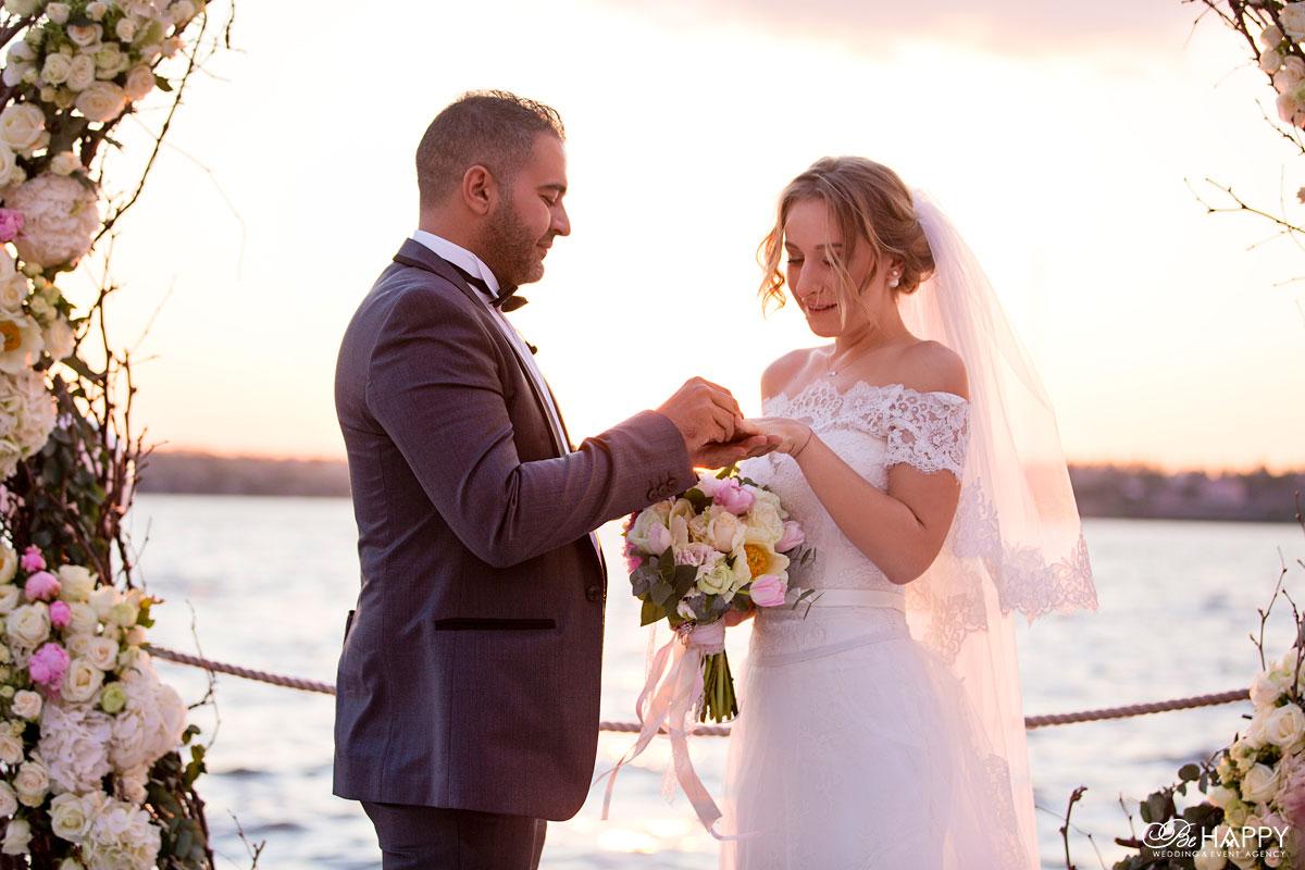 Жених надевает на палец невесты обручальное кольцо бихеппи