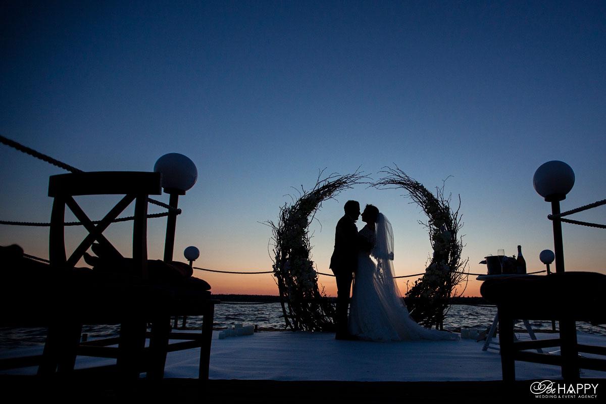 Силуэтное фото жениха и невесты возле свадебной арки
