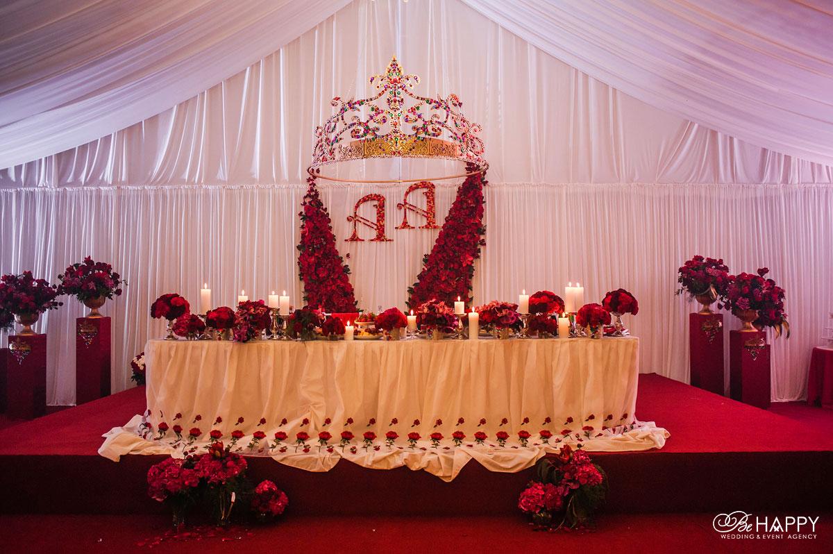 Красные цветы и свечи на столе молодоженов