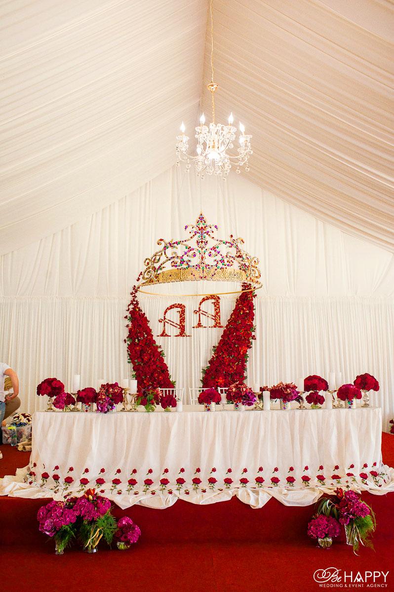 Стол молодоженов, украшенный красными цветами