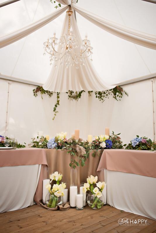 Стол молодоженов, украшенный живыми цветами и свечами в шатре для банкета