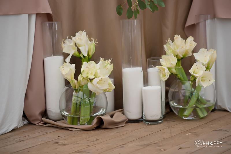 Живые цветы в круглых вазах и белые свечи свадебный декор