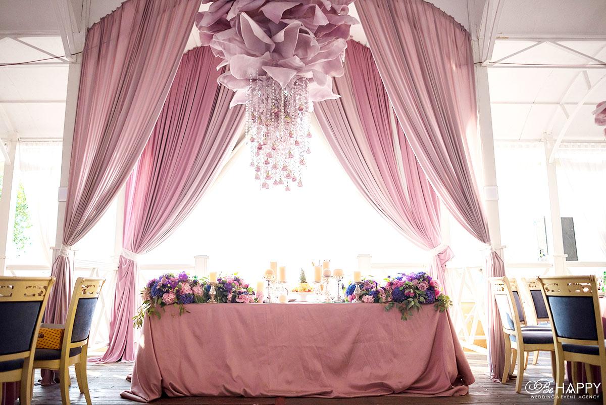 Стол молодоженов, драпированный тканью и украшенный цветами