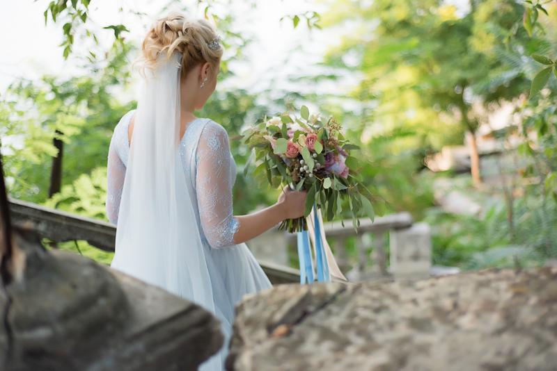 Невеста спускается по лестнице с букетом в руках