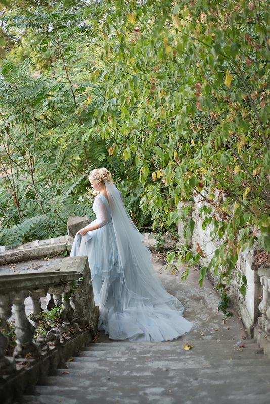 Фото невесты в свадебном платье со шлейфом, идущей по лестнице