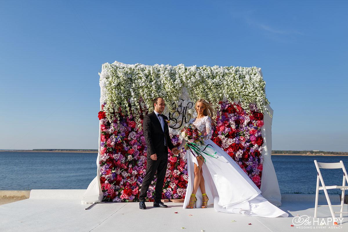 Жених и невеста на фоне арки, украшенной цветами