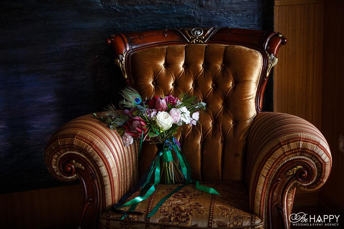 Букет невесты с пером павлина на кожаном кресле