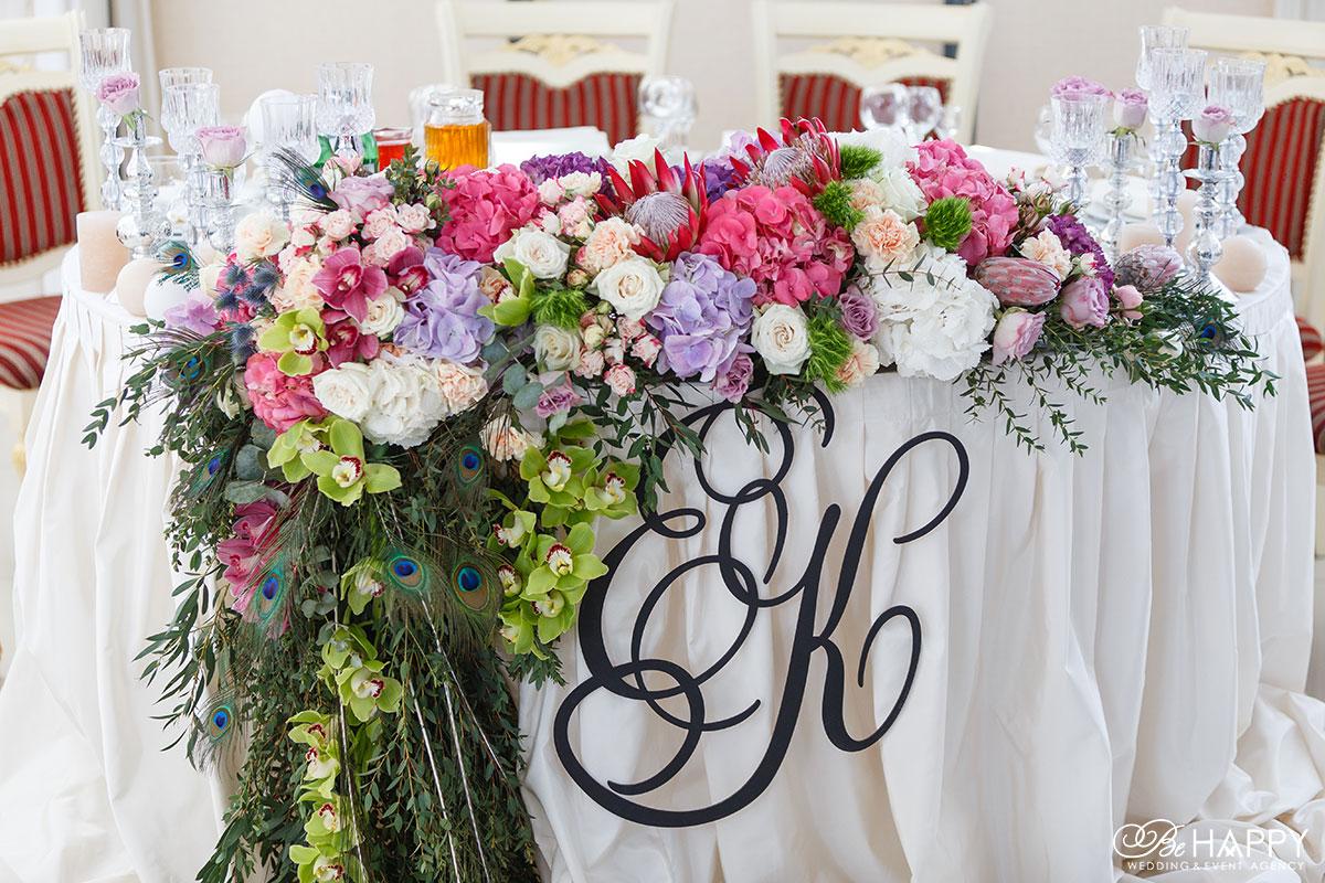 Стол жениха и невесты с инициалами, живыми цветами и перьями павлина
