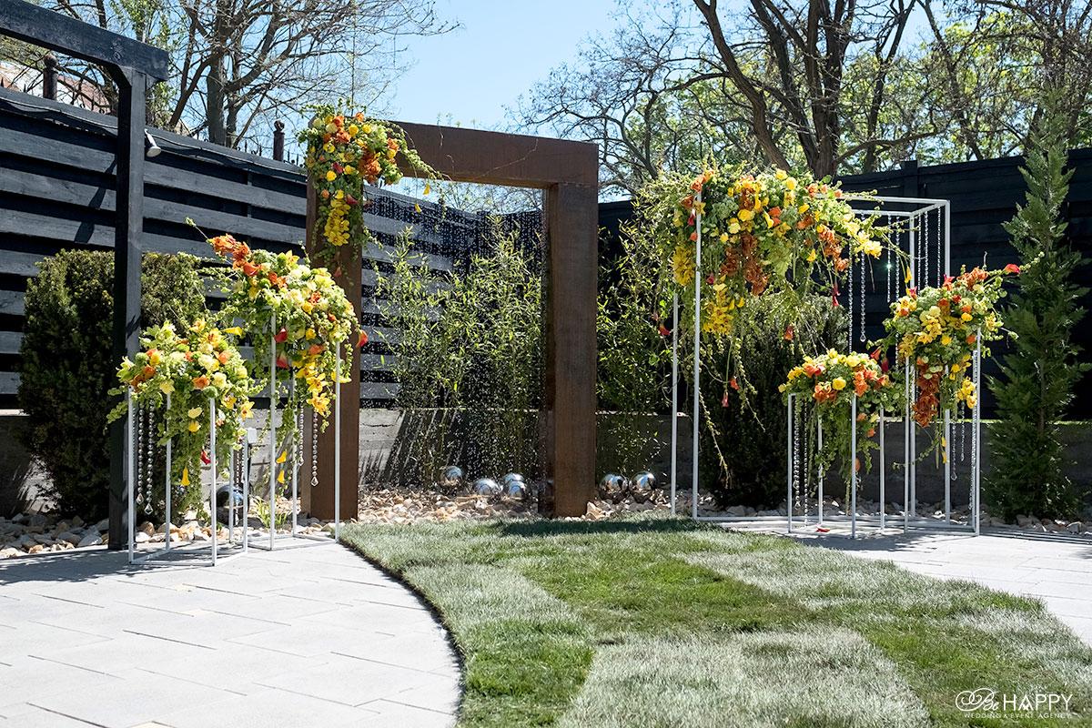 Деревянная свадебная арка и цветочные композиции в зоне церемонии