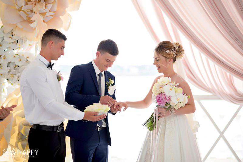 Молодожены обмениваются кольцами на фоне свадебной арки Николаев