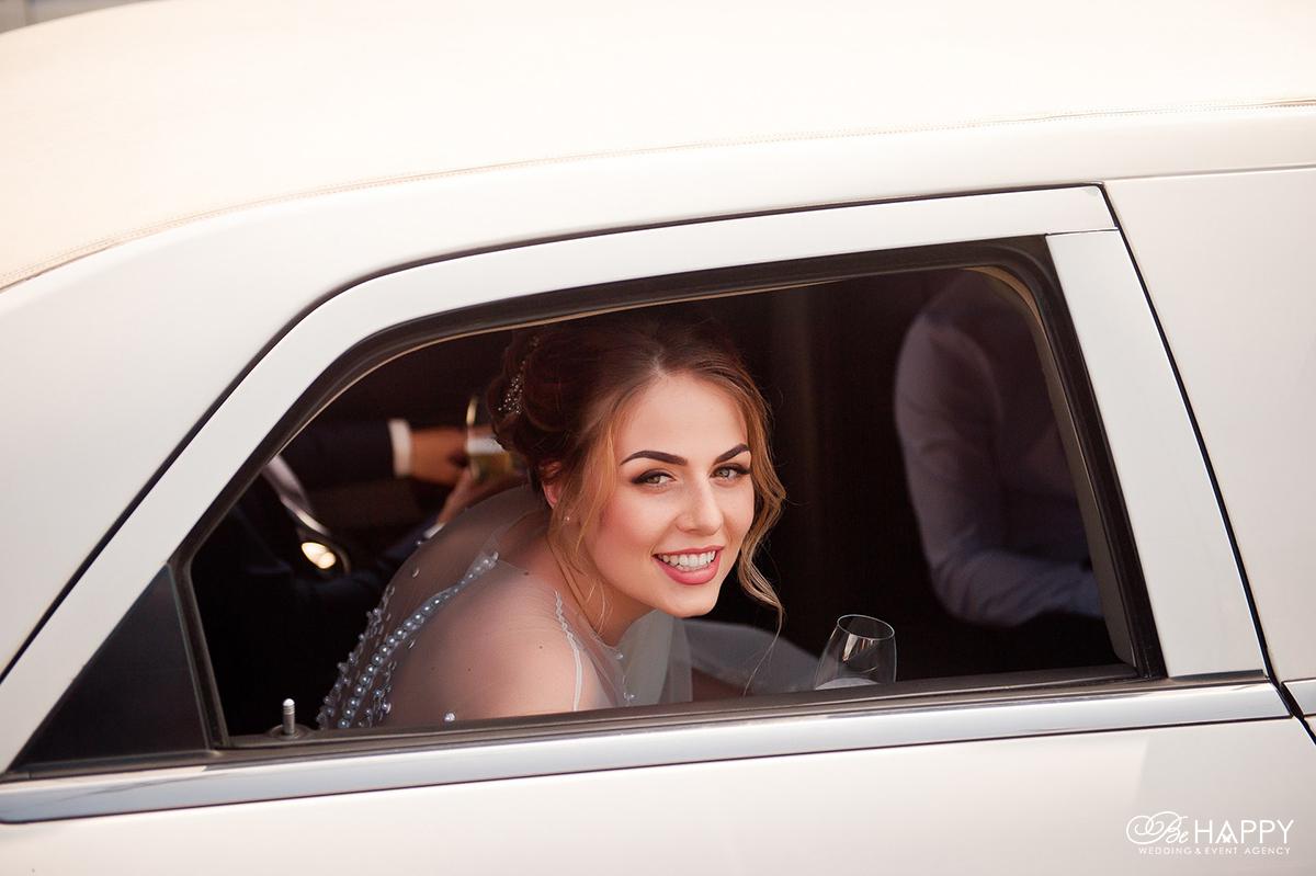 Фото невесты в свадебном автомобиле с бокалом шампанского