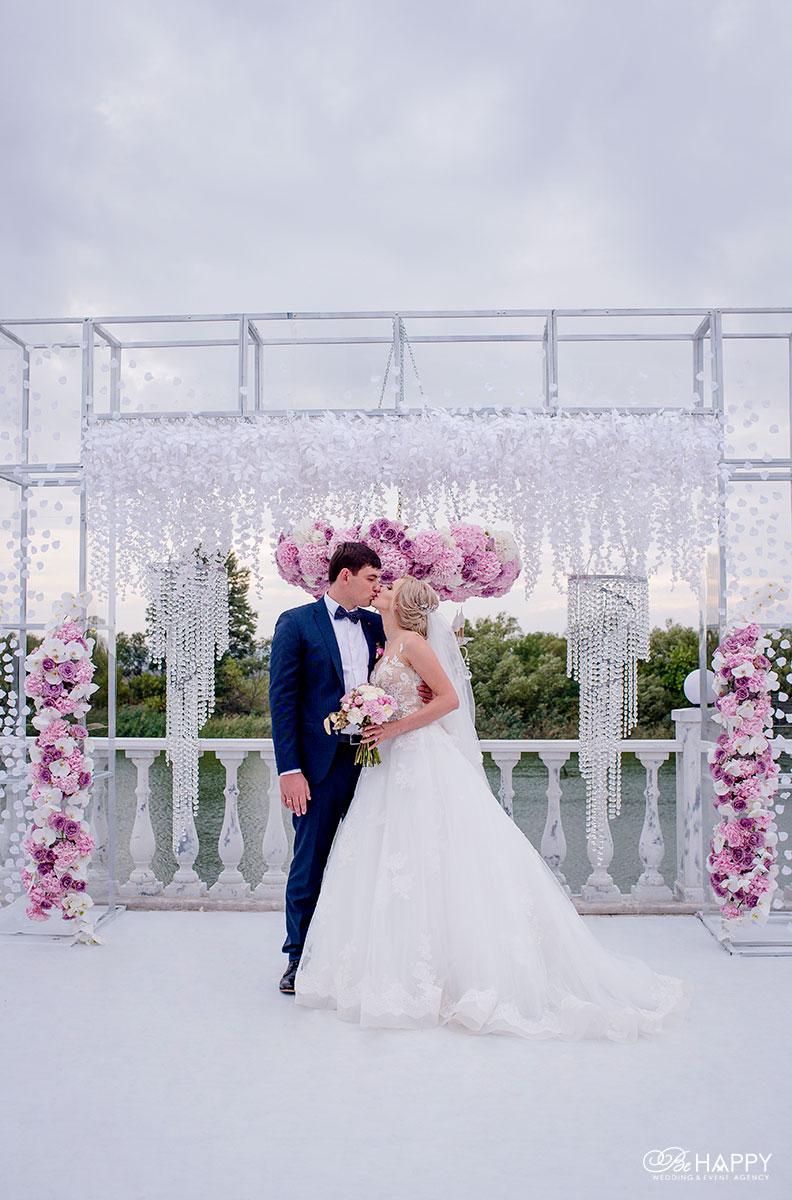 Фото первого поцелуя молодоженов на фоне свадебной арки Би Хеппи