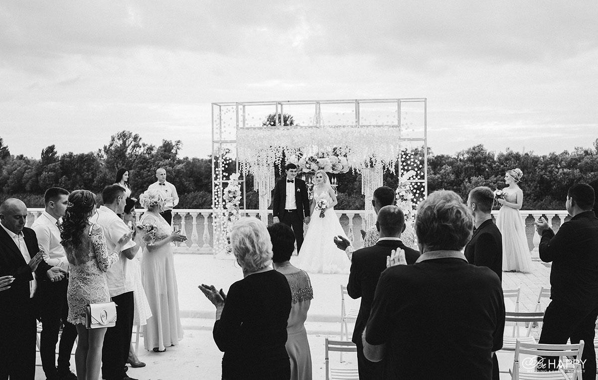 Черно-белое фото молодоженов и гостей свадьбы бихеппи