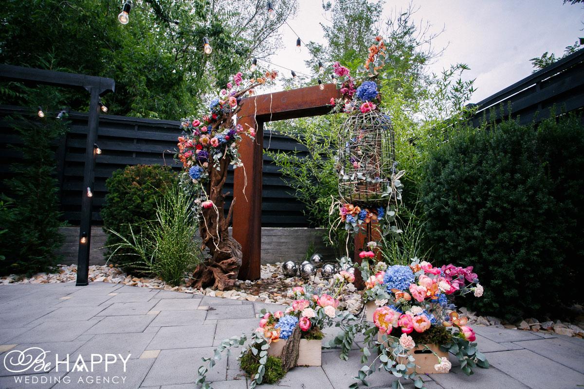 Деревянная свадебная арка с живыми цветами и птичьей клеткой