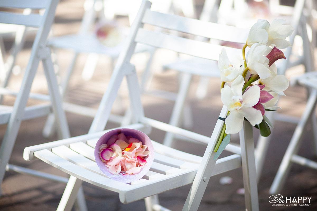 Живые орхидеи и лепестки роз на местах для гостей