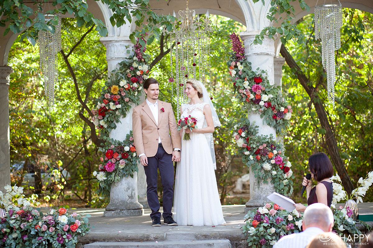 Фото жениха и невесты на фоне свадебной арки Би Хеппи