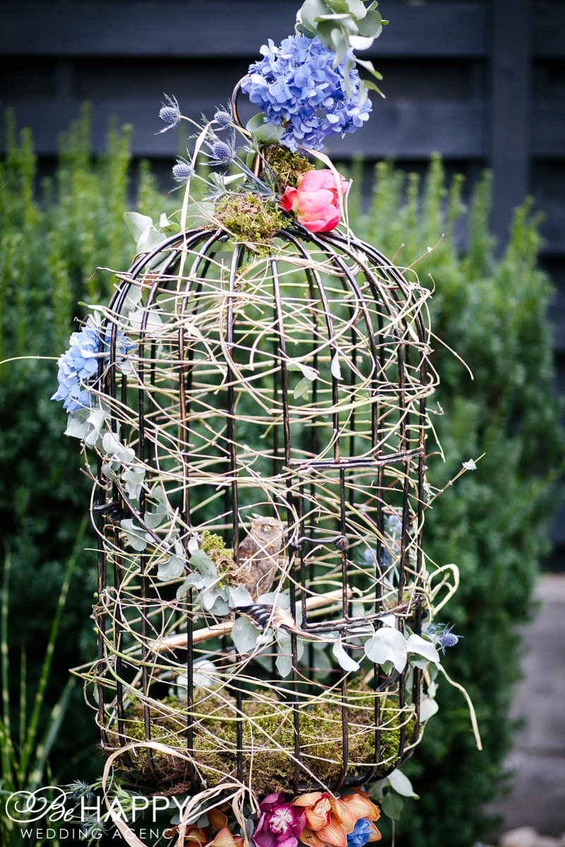 Фото декоративной птичьей клетки с совой и живыми цветами