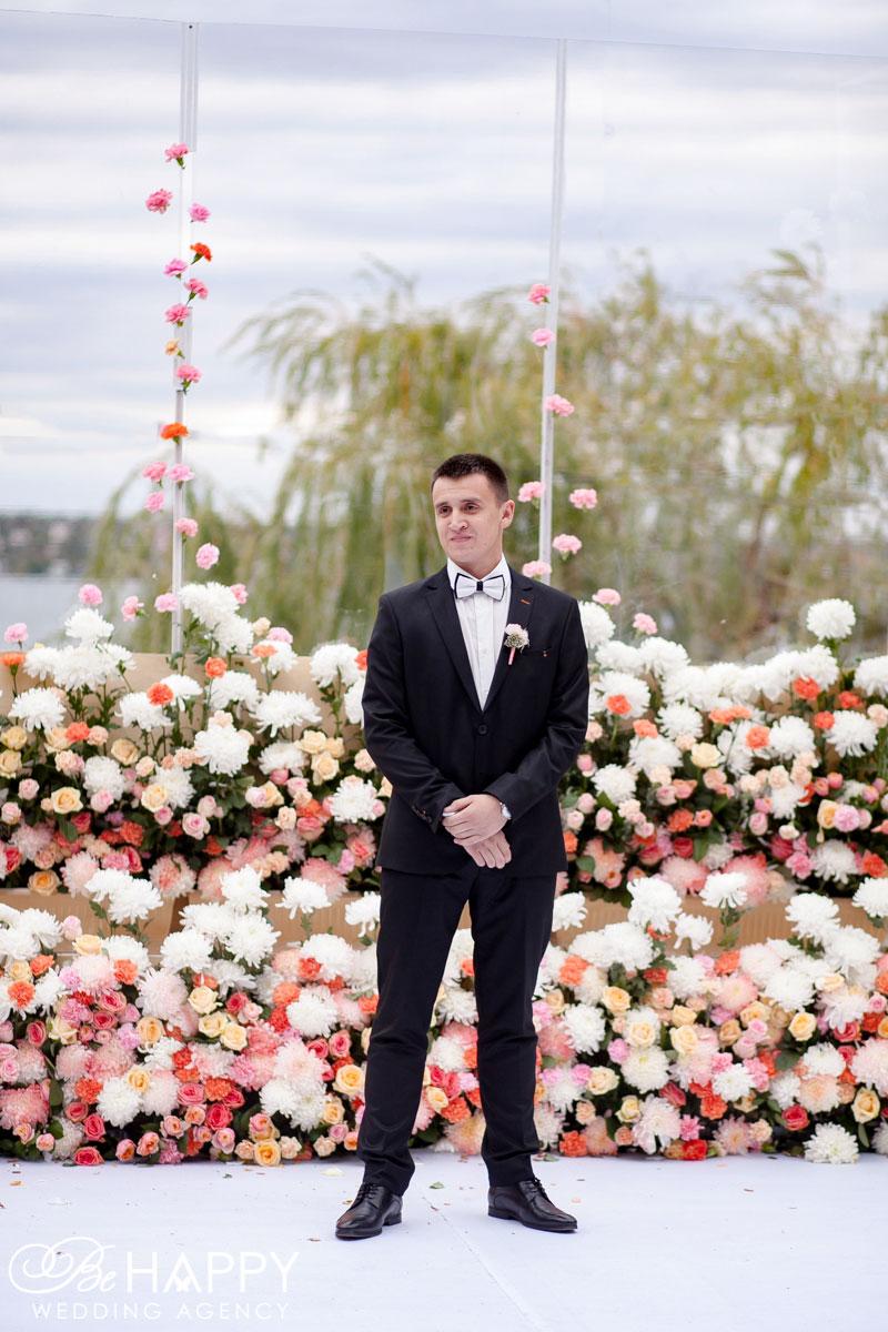 Фото жениха в смокинге на фоне свадебной арки