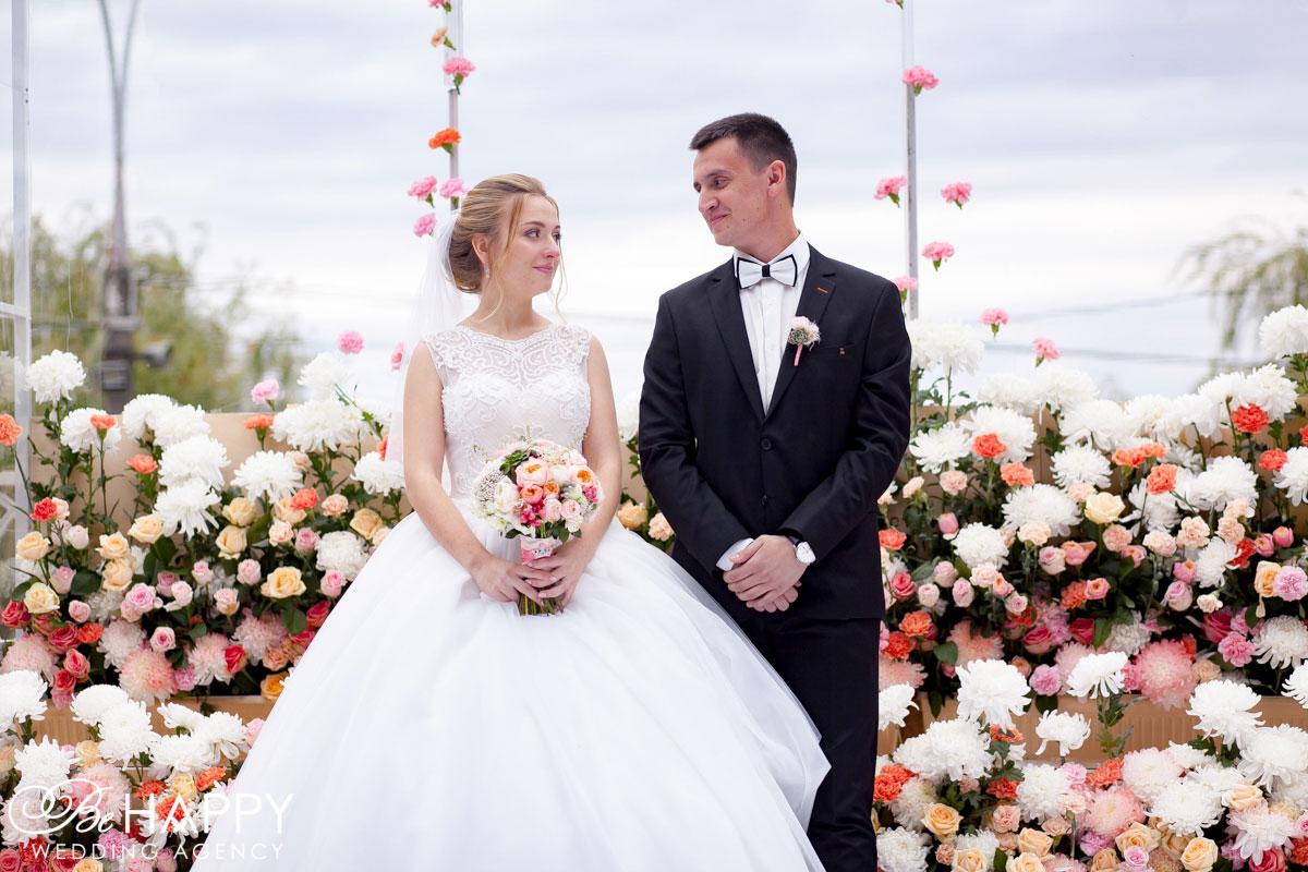 Фото молодоженов на фоне нежной свадебной арки