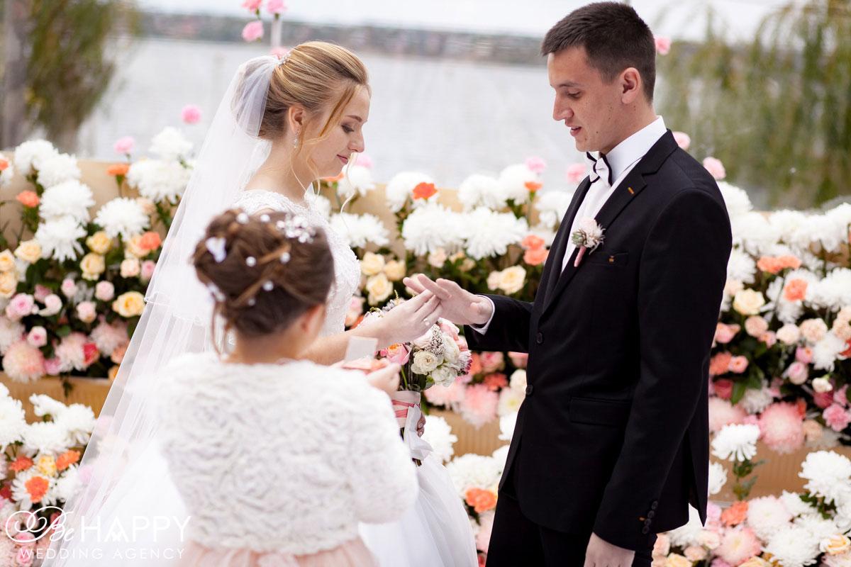 Невеста надевает обручальное кольцо на руку жениха свадьба Николаев
