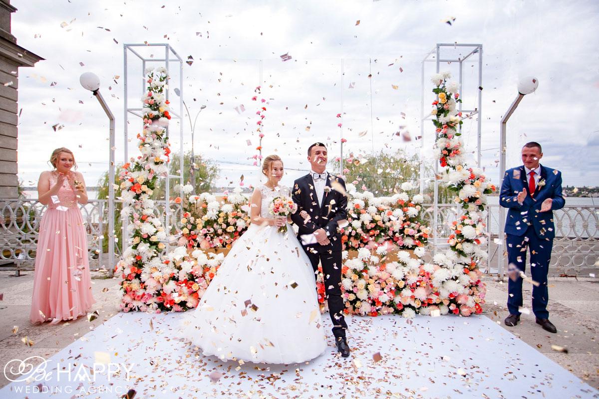 Гости посыпают молодоженов лепестками роз свадьба Николаев