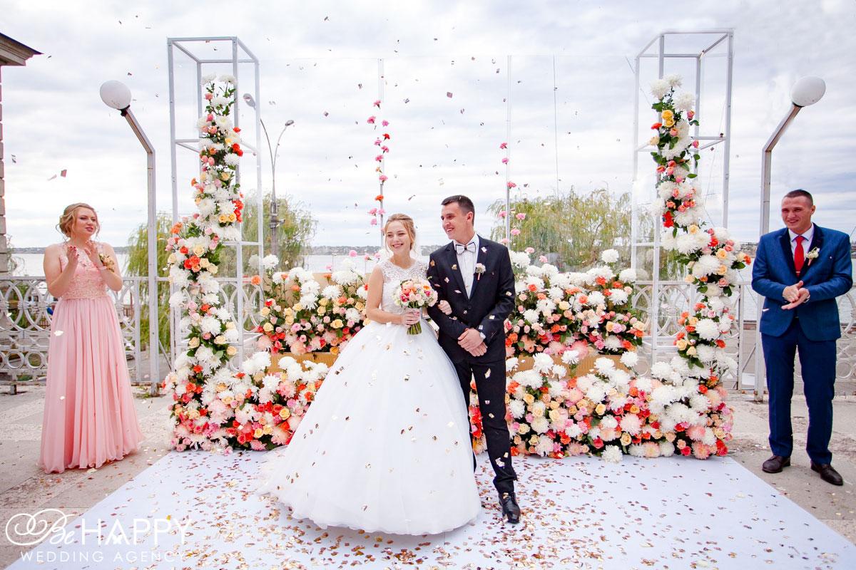 Фото молодоженов и свидетелей на фоне свадебной арки с живыми цветами Николаев