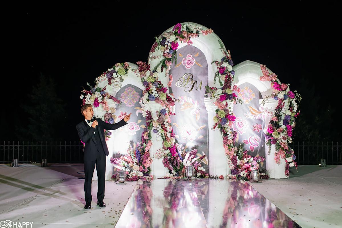 Ведущий Владимир Остапчук на фоне свадебной арки фото