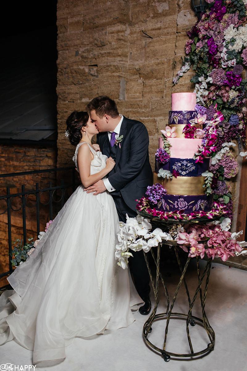 Фото целующихся молодоженов около свадебного торта