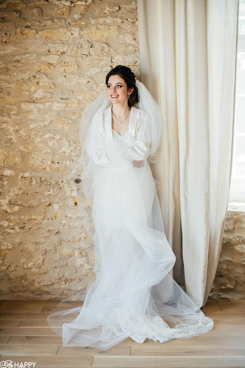 Фото невесты в воздушной фате возле окна