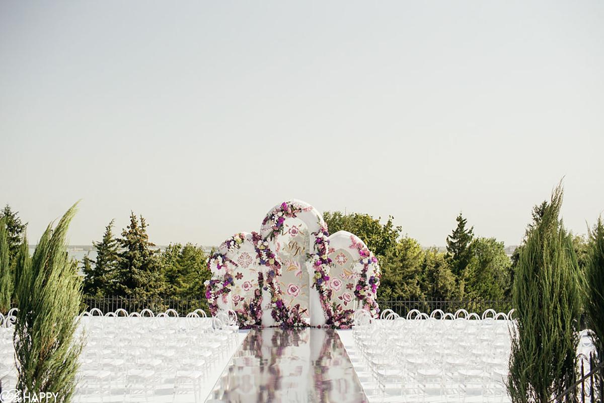 Свадебная арка с живыми цветами на фоне деревьев