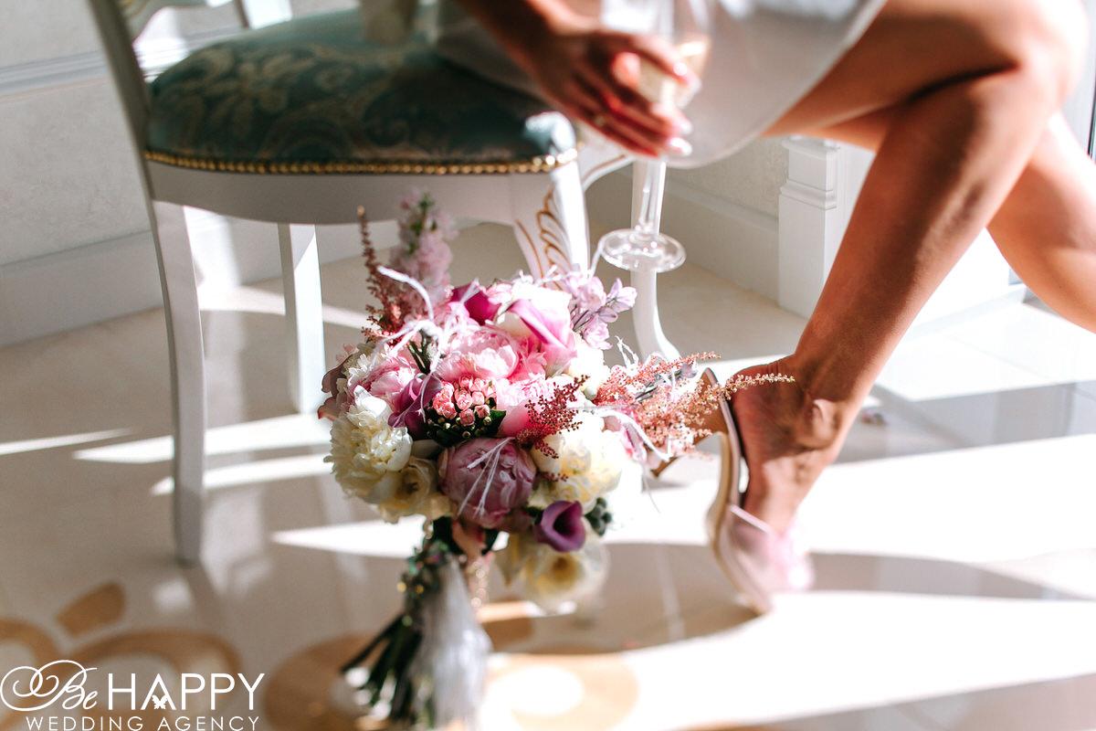 Фото невесты с бокалом в руке и свадебным букетом на полу
