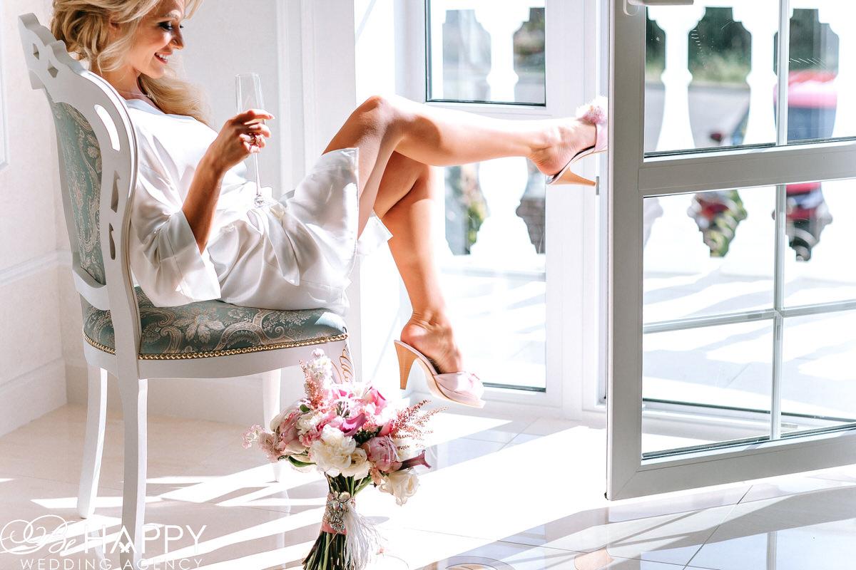Невеста пьет шампанское сидя на стуле свадебная фотосессия
