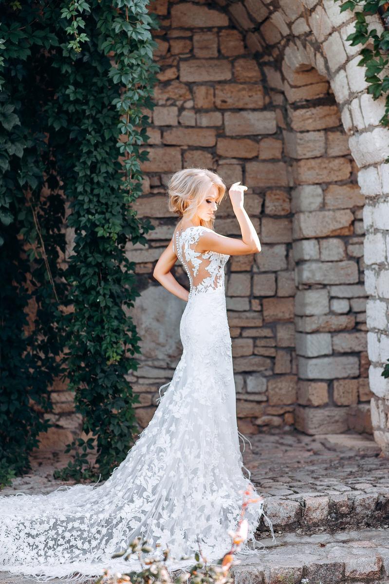 Невеста позирует фотографу в свадебном платье с длинным шлейфом