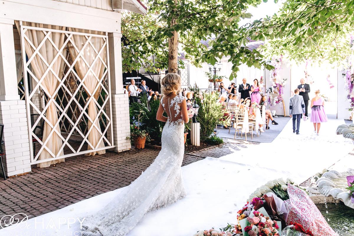 Невеста в свадебном платье с длинным шлейфом идет по проходу