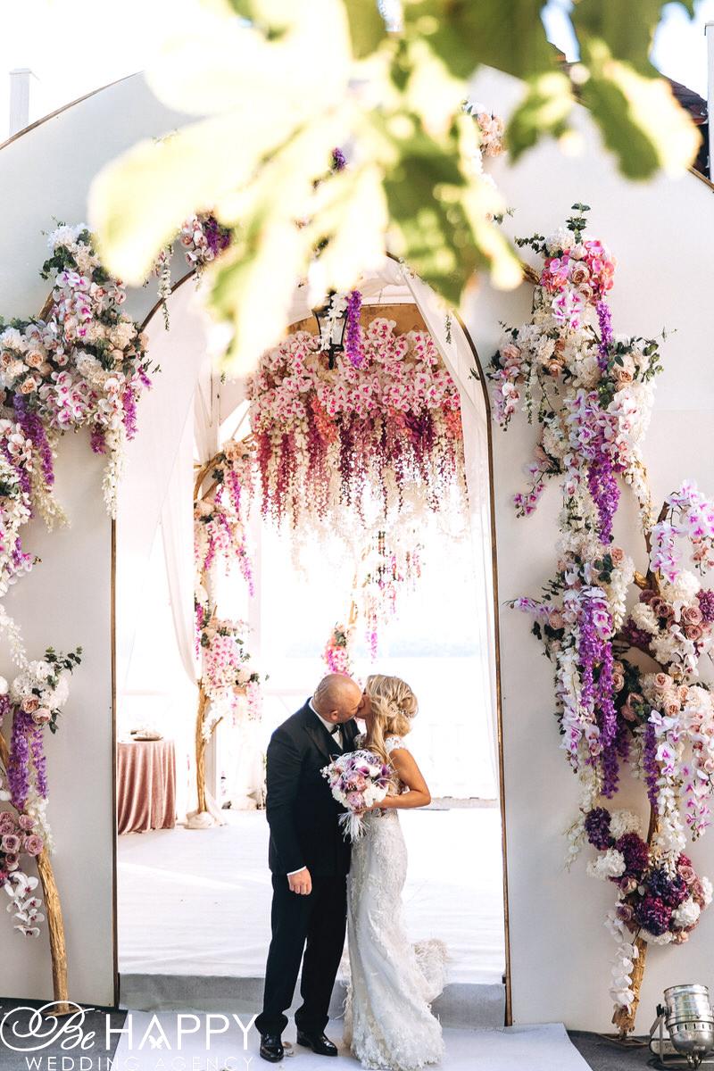 Поцелуй невесты и жениха на фоне свадебной арки с цветами
