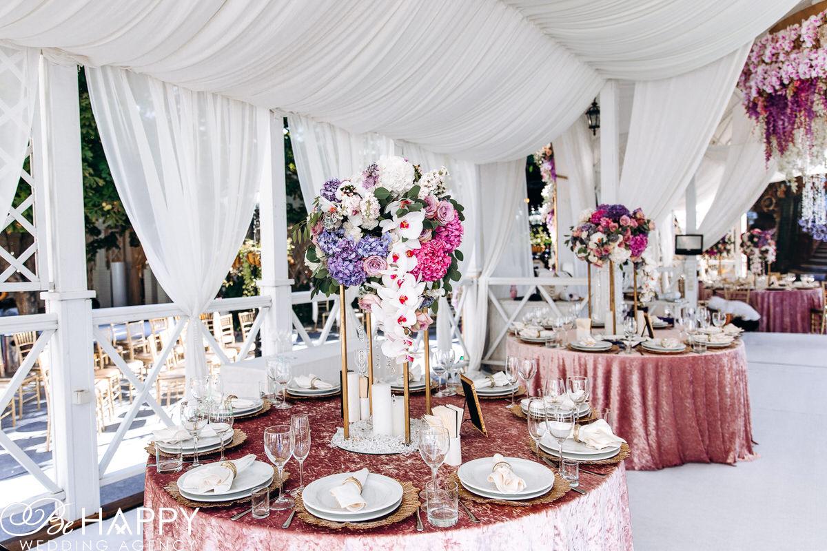 Букеты из свисающих орхидей, роз и гортензий на столах для гостей