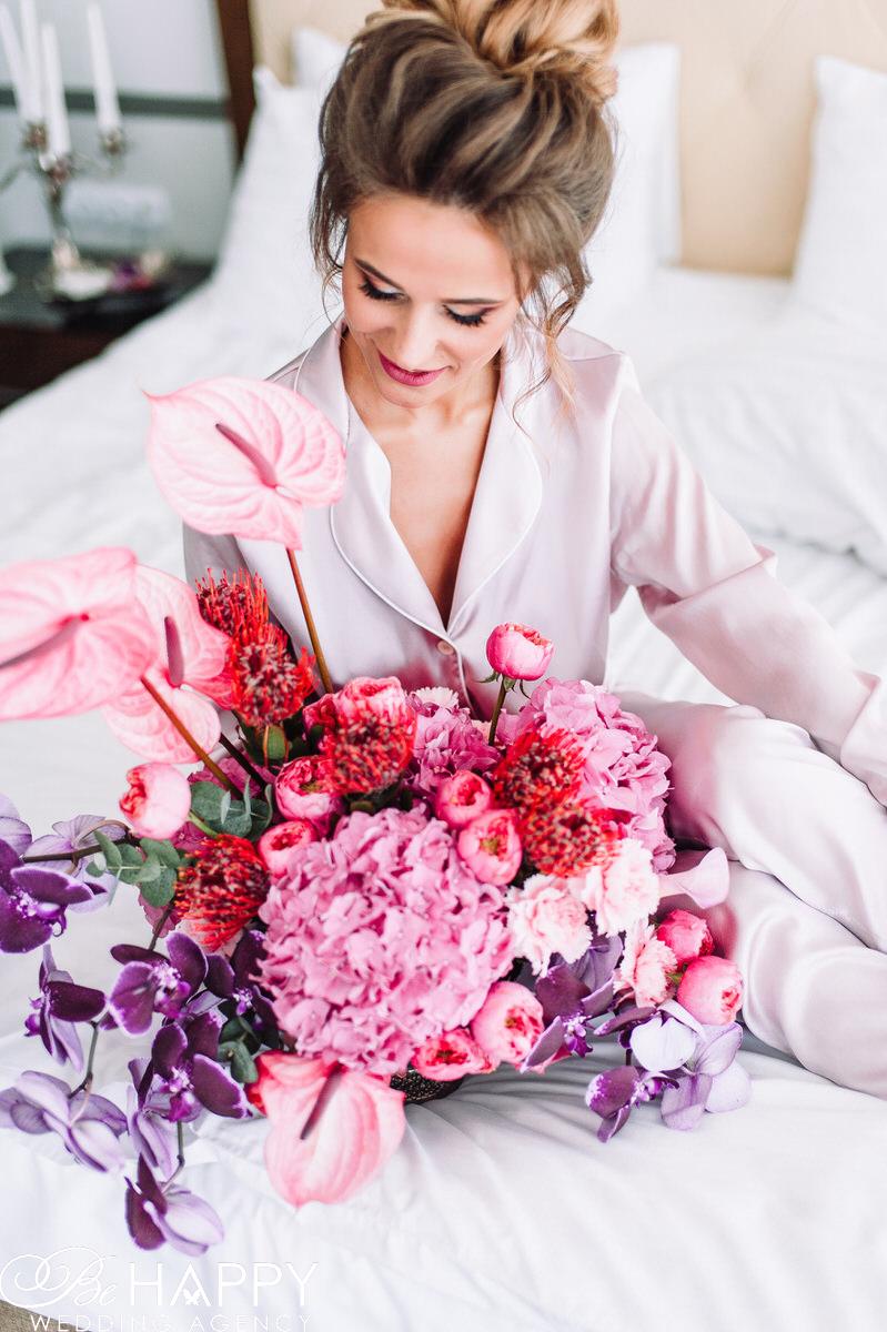 Фото невесты в шелковой пижаме со свадебным букетом