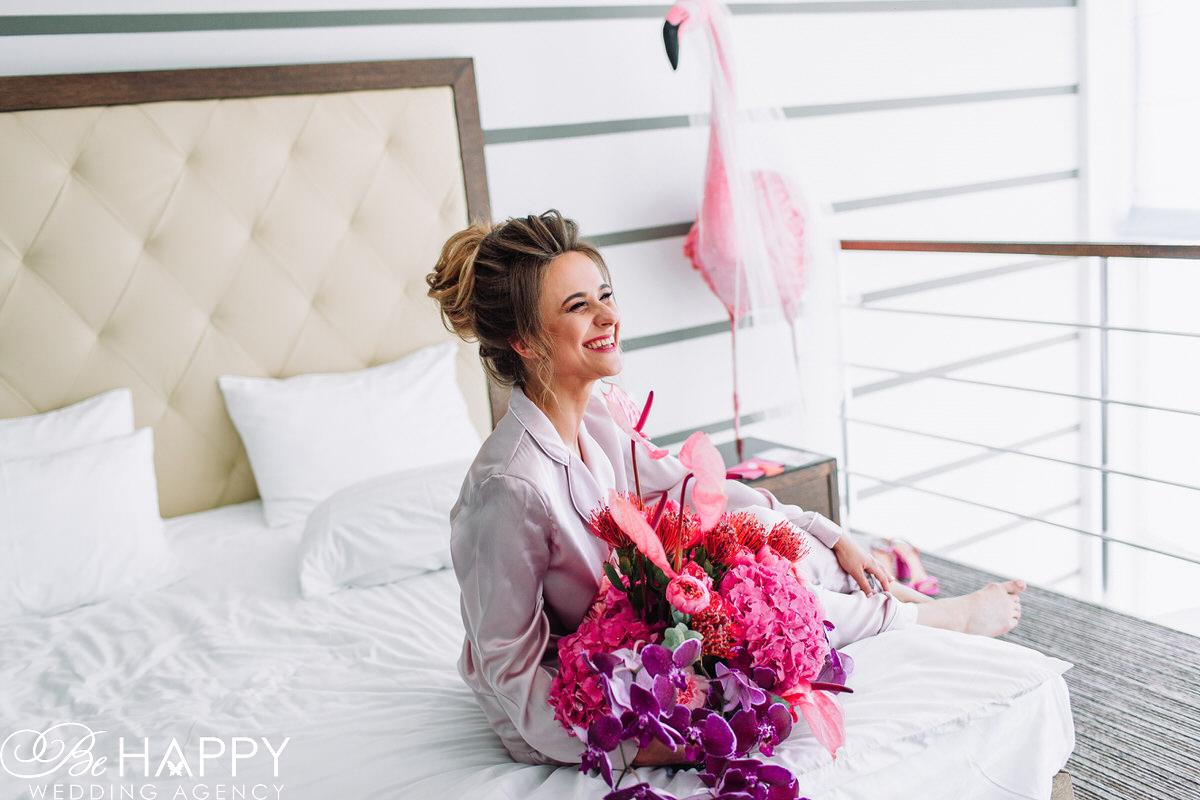 Улыбающаяся невеста сидит на кровати с букетом в руках