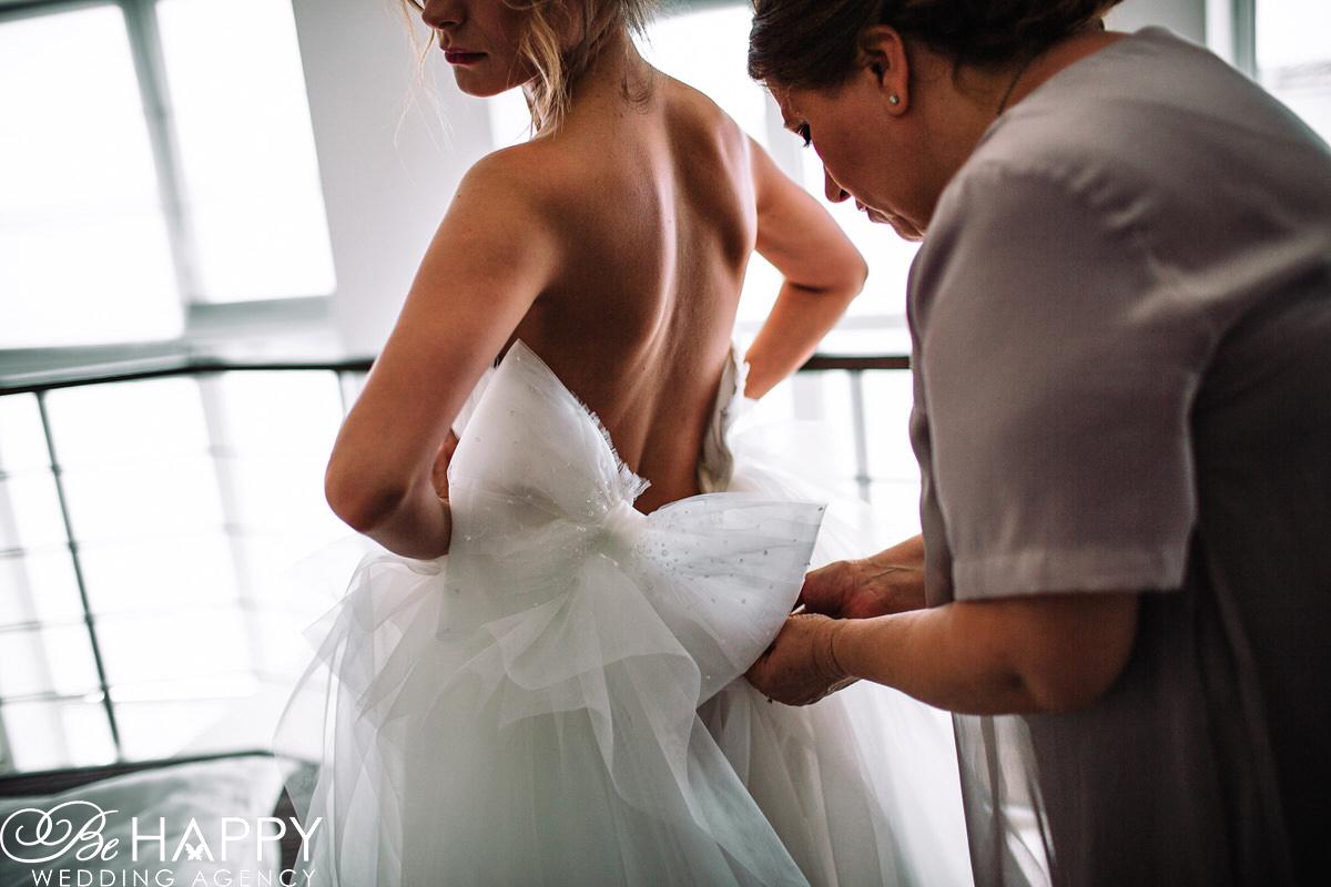 Невесте помогают застегнуть свадебное платье