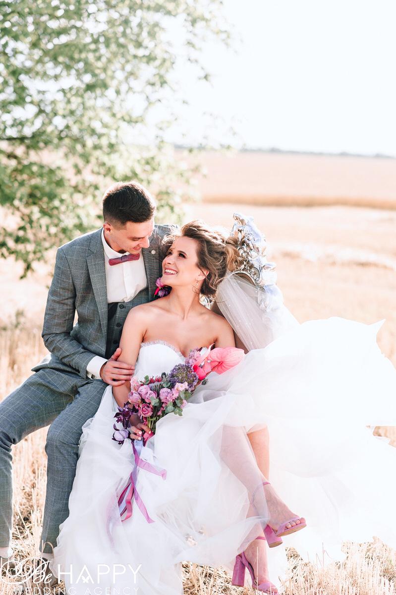 Фото улыбающихся жениха и невесты в поле