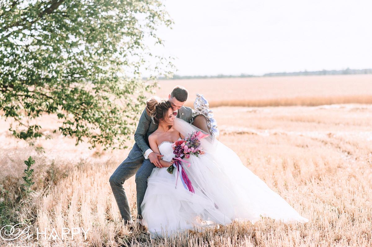 Жених и невеста сидят на стуле в поле фото